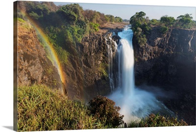 Rainbow formed in mist from waterfall, Victoria Falls, Zimbabwe