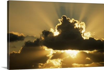 Sun rays beam from behind cumulus clouds