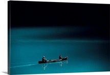 A canoe plies the mirror smooth surface of Lake Louise