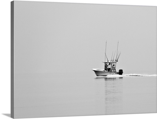 A fishing boat plows through calm waters on an ovcercast day Wall ...