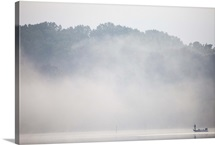 A lone fisherman in a boat in heavy fog at sunrise on the Occoquan River