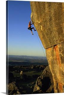 A man climbs a large rock face at the Rocklands