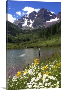 A man fishing in a scenic mountain lake near the Maroon Bells peaks