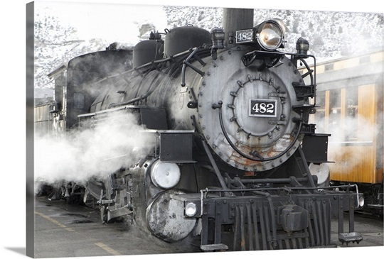 A narrow gauge steam train sitting at station