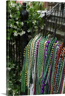 An iron gate covered with Mardi Gras beads in front of a house