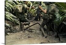 Armed South Vietnamese marines slog through jungle mud