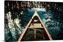 Bow of a canoe set against reflected trees, Georgia