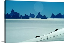Expedition members ski past the peaks of Fenriskjeften, Antarctica