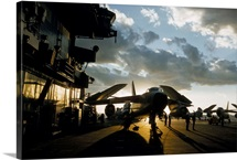 Silhouetted mechanics ready Skywarrior jets for night operations