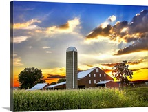 Silo, barn, and cornfield of an American farm backlit at sunset
