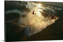 Ultralights fly over mile wide Victoria Falls on the Zambezi River in Zimbabwe