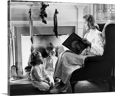 1940s 1950s Mother Reading Christmas Story, Sitting By Fireplace Hung With Stockings