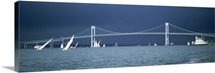A storm approaches sailboats racing past Rose Island lighthouse and the Newport Bridge in Narragansett Bay, Newport, Rhode Island USA