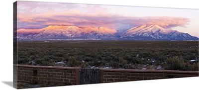 An adobe brick wall and Sangre De Cristo Mountains, New Mexico