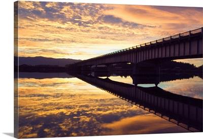Cloudy sunset sky over bridge, reflection in Flathead River, Montana