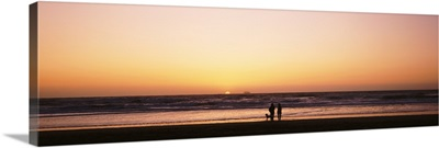 Couple w/ dog at sunset on Ocean Beach Southern CA