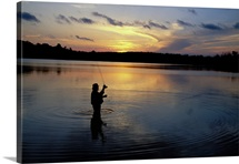 Fly-fisherman silhouetted by sunrise, Mauthe Lake, Kettle Moraine State Forest, Wisconsin