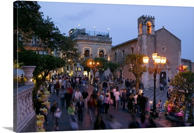 Group of people on the street at dusk, Piazza IX Aprile, Taormina, Sicily, Italy