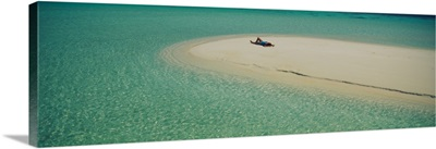 High angle view of a woman sunbathing on the beach, Maldives