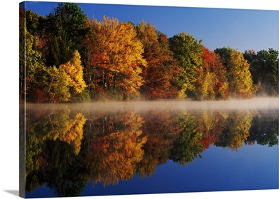 Layer of mist on Hidden Lake, autumn color trees with water reflection, Delaware Water Gap National Recreation Area, Pennsylvania