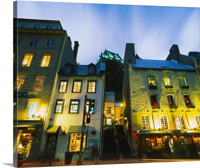 Low angle view of buildings lit up at dusk, Quebec, Canada