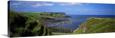 Lush green coastal cliffs, blue sea, Northern Ireland