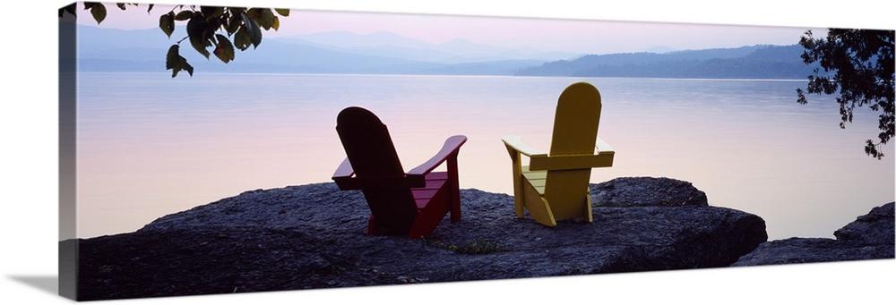 Red and Yellow Adirondack chairs on a rock near a lake, Champlain Lake,  Vermont