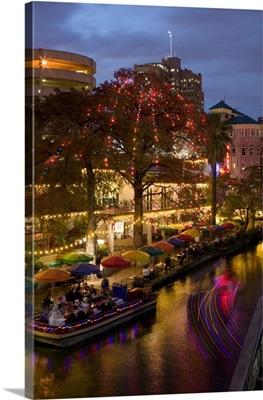 Restaurant along a river lit up at dusk, San Antonio River, San Antonio, Texas