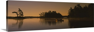Silhouette of a person in a canoe on a lake, Kejimkujik Lake, Kejimkujik National Park, Nova Scotia, Canada