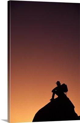 Silhouetted backpacker on rock, sunset light, Utah