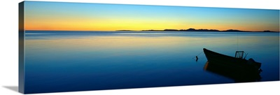 Silhouetted boat moored in Chukchi Sea at sunset, distant Mulgrave Hills, Alaska