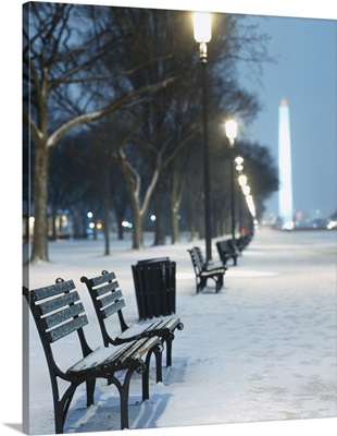 Snow covered benches along a footpath, Washington Monument in background, Washington DC