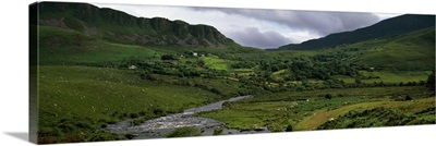 Stream through lush mountain landscape, distant cottages, Ireland