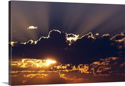 Sun rising behind dark clouds, Montana