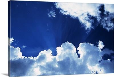 Sunbeams behind billowing white clouds, blue sky.