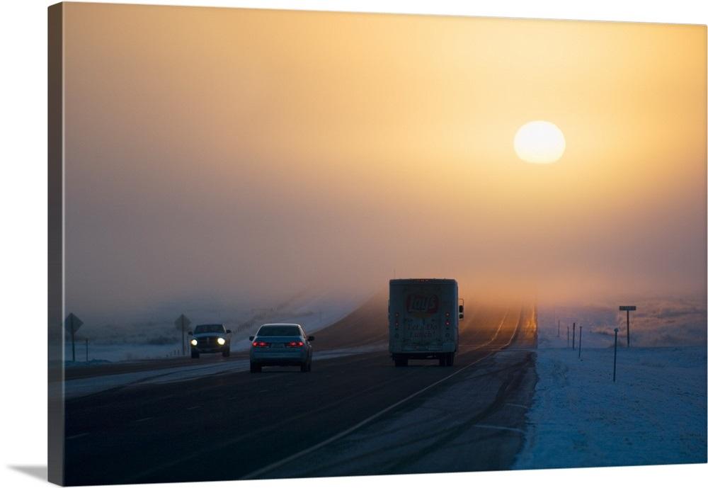 Sunrise over highway traffic, winter fog