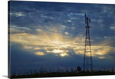 Sunset light through heavy clouds, silhouetted windmill, Iowa