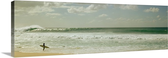 Surfer standing on the beach, North Shore, Oahu, Hawaii,
