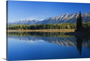 Swan Mountain Range Reflecting In Calm Water Of Rainy Lake