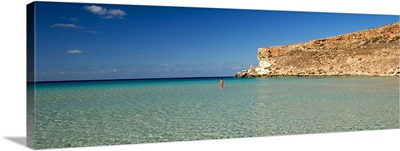 Tourist walking in the sea, Spiaggia Dei Conigli, Italy