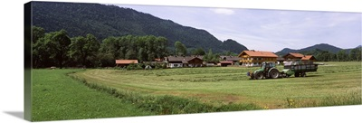 Tractor collecting hay in a farm, Bad Tolz, Bavaria, Germany