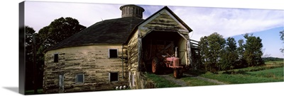 Tractor parked inside of a round barn, Vermont,