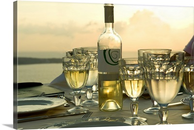Wine glasses with a wine bottle on a table, Santorini, Cyclades Islands, Greece