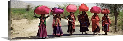 Women standing on a road with luggage on their head, Siana, Jodhpur, Rajasthan, India