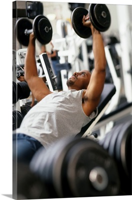 Male working out with weights in a health club
