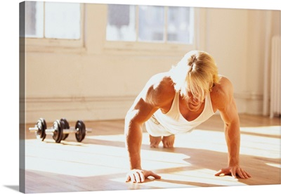 Young man performing push up exercise in gym