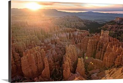 The sun on the horizon shining on the hoodoos in Bryce Canyon Amphitheater, Utah