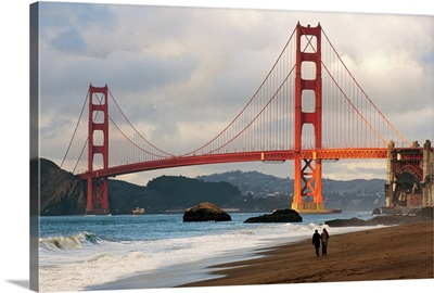 A couple strolling on Baker Beach near the Golden Gate Bridge at dawn