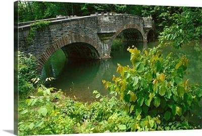 A stone bridge crosses the headwaters of the Susquehanna River, New York