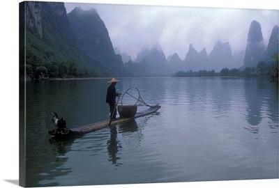 Cormorant fisherman poles a bamboo raft near limestone karst mountains, Li River, People's Republic of China